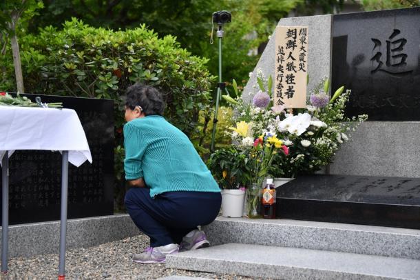 関東大震災での朝鮮人犠牲者を悼み、慰霊碑の前にしゃがみこむ女性=1日午前10時17分、東京都墨田区の都立横網町公園20170901