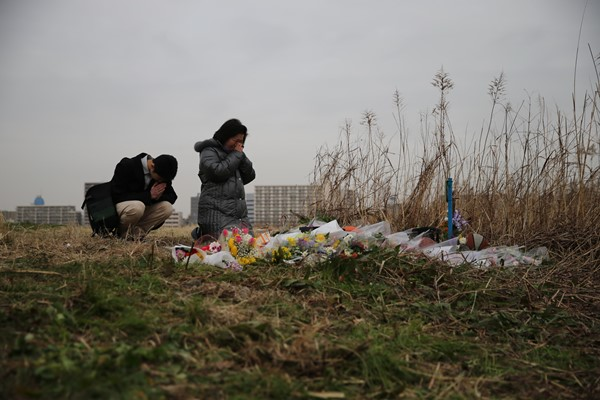 殺害された中学1年の少年の遺体発見現場を近所の女性が訪れ、手を合わせていた=2015年2月25日、川崎市川崎区港町の河川敷