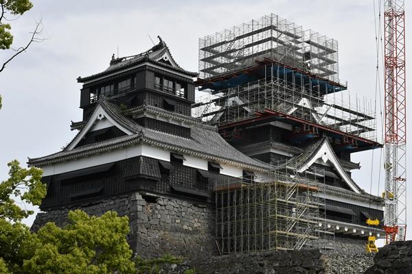 修復のため解体作業が進む熊本城の大天守(右)。左は小天守=2017年5月13日、熊本市