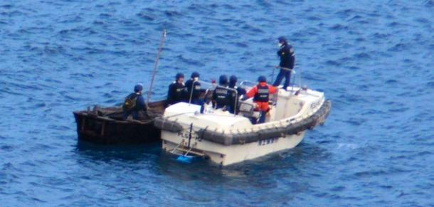 不審船とみられる船と海上保安部のボート=6日午後4時26分、隠岐の島町那久 201201