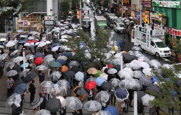 雨の中、街頭演説を聞く有権者たち=10月15日、東京都内(選挙カーなどにモザイクをかけています)