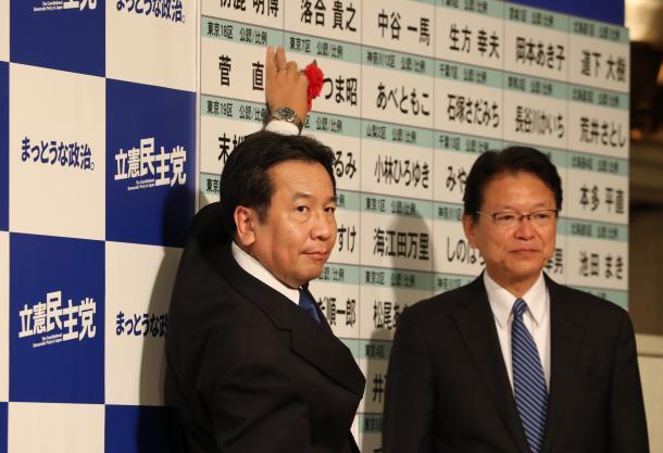 当選を決めた候補者名に花をつける立憲民主党の枝野幸男代表(左)。右は長妻昭代表代行=10月22日、東京都港区