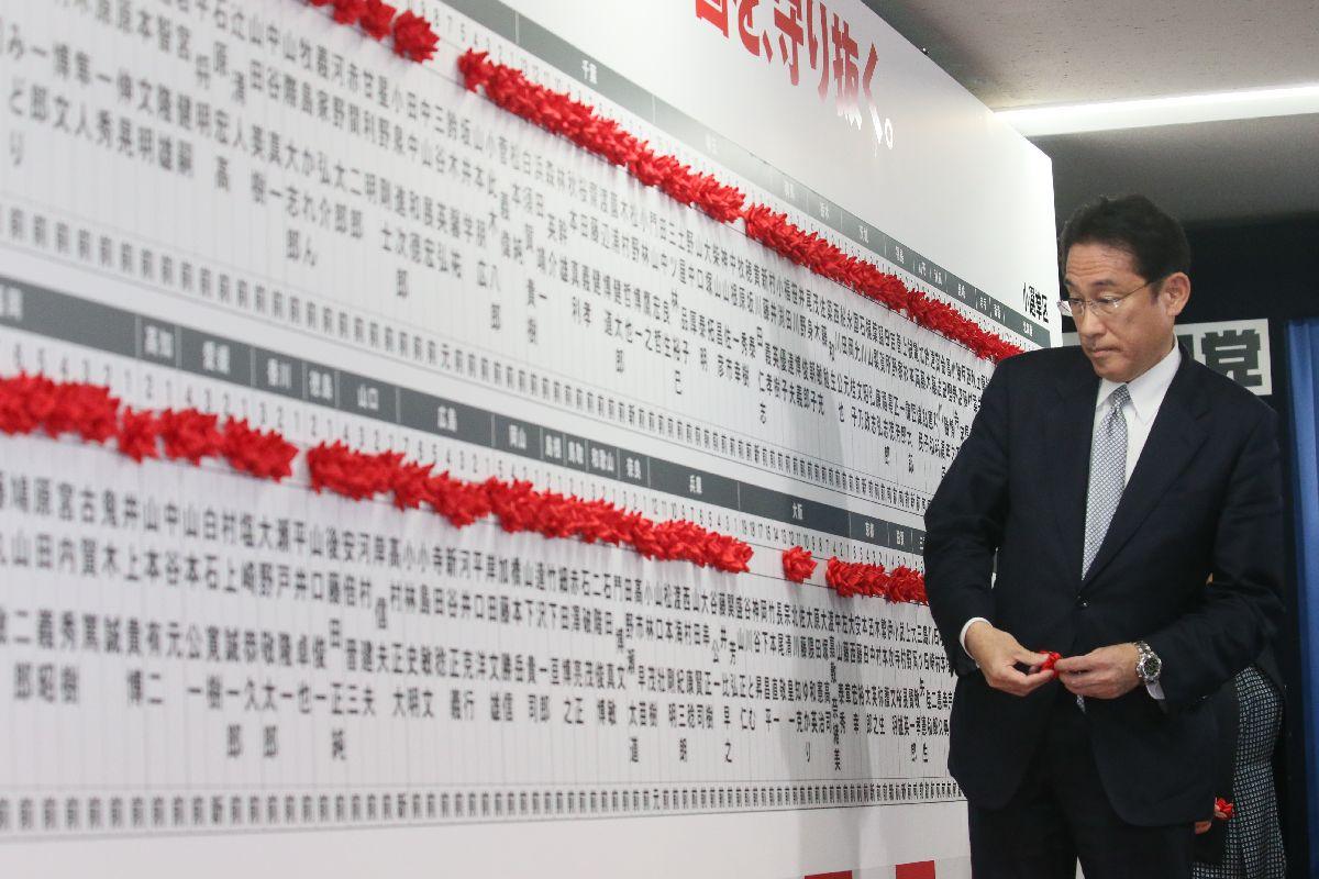 当選を決めた候補者名に花をつける自民党の岸田文雄政調会長=10月22日午後11時36分、東京・永田町
