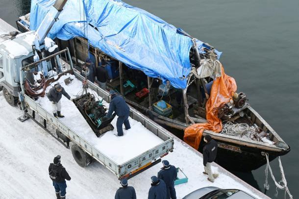 木造船の内部から機器を運び出す捜査員や関係者=9日午前9時41分、北海道函館市