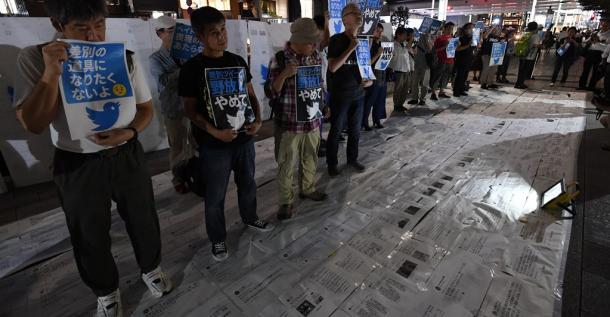 路上にヘイトスピーチが書かれたツイートを敷き詰めて踏みつける参加者。歩行者にもツイートを踏んで通るよう呼びかけていた=8日午後6時25分、東京都中央区