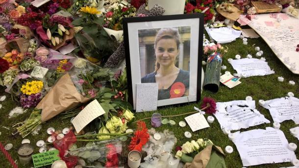 殺害されたコックス議員の写真の周りに、たくさんの人が追悼の花束を置いた=2016年6月、パーラメント広場