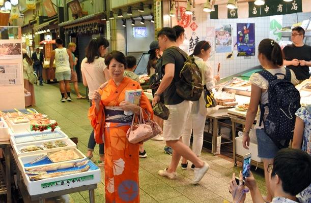 イカの串焼きを手に着物姿で記念撮影する外国人観光客=2017年7月11日、京都市中京区の錦市場