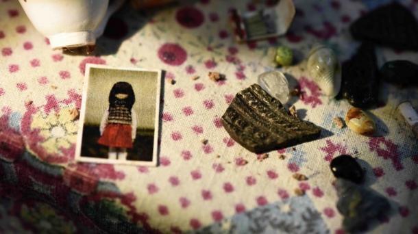『松が枝を結び』(2017年)監督・脚本/村田朋泰 「生と死にまつわる記憶の旅」第3幕。画像は震災で家の中に散乱した品々と亡くなった少女の写真