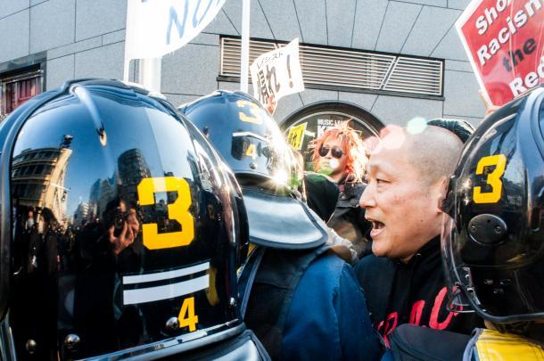 在特会などの極右、排外デモへのカウンター行動。排外主義者のデモ隊へ機動隊に囲まれながら抗議するECDさん=2014年3月16日、東京・池袋(写真家・島崎ろでぃー撮影)