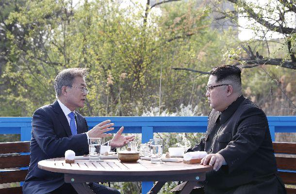 ベンチに座って話し込む韓国の文在寅大統領(左)と北朝鮮の金正恩委員長(右)=4月27日、板門店