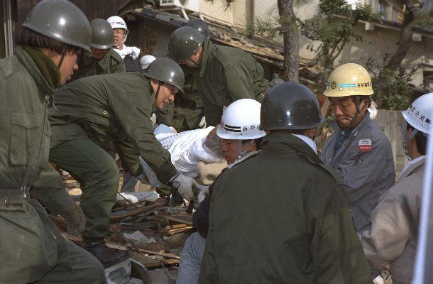 阪神大震災で崩壊した家屋から救出された被災者。自衛隊員たちが担架で運ぶ=1995年1月18日、兵庫県西宮市北口町