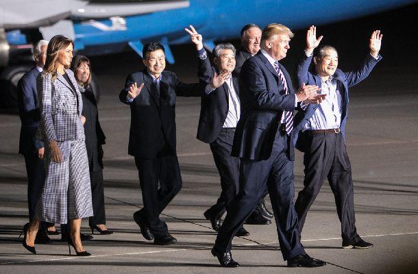 北朝鮮から解放されて帰国した3人を出迎えたトランプ大統領(右から2人目)=2018年5月10日、米ワシントン郊外のアンドルーズ空軍基地