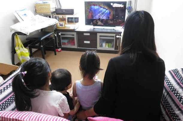 3人の子どもとテレビに見入る育児休業中の女性。「早く仕事に復帰したい」=2016年8月、東京都武蔵野市