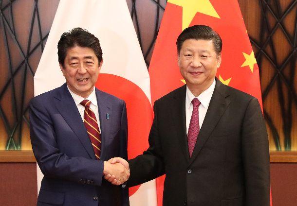 米中首脳会談の冒頭、握手する中国の習近平国家主席(右)と安倍晋三首相=2017年11月11日、ベトナム・ダナン
