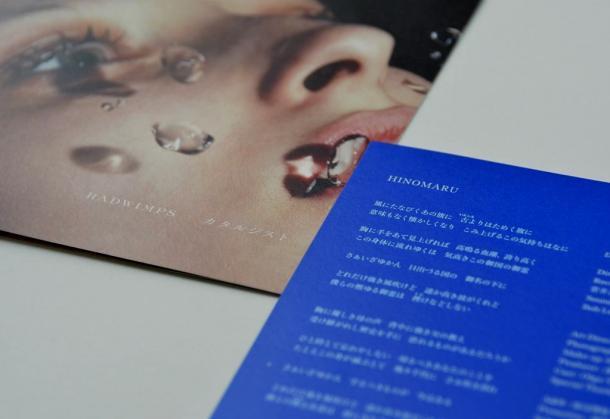RADWIMPSの新曲「HINOMARU」の歌詞カード(右下)と、同曲を収録したCDのジャケット